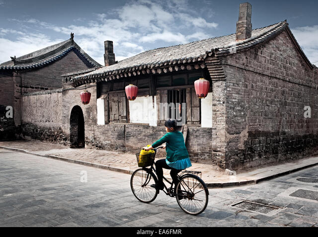 China, Pingyao, Girl riding bicycle - Stock Image