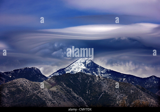 Strange (lenticular) cloud, over Mavrovouna, one of the highest summits of Taygetos mountain. Peloponnese, Greece. - Stock Image