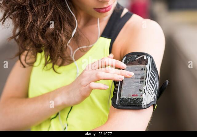 Cropped close up of female runner choosing music on smartphone armband - Stock Image
