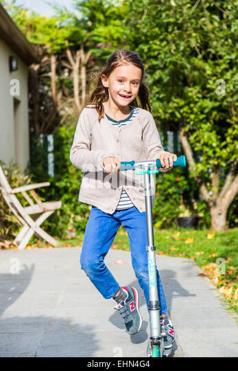 Children on scooters outdoors. - Stock Image