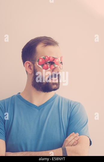 Superhero wearing mask with strawberries, daydreaming - Stock-Bilder