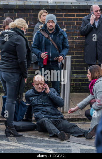 London, UK. 9th Jan, 2017. A man collapses and is helped by other waitng commuters - Clapham Junction Station is - Stock Image