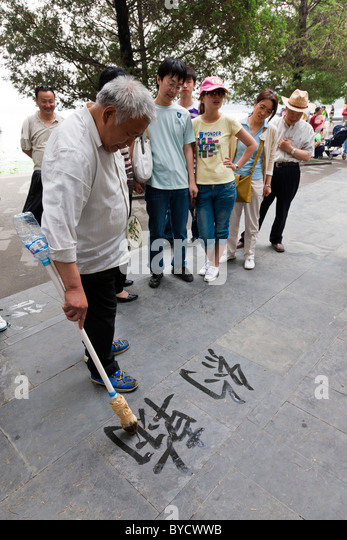Old Chinese man practicing street calligraphy in the grounds of the New Summer Palace, Beijing, China. JMH4797 - Stock Image