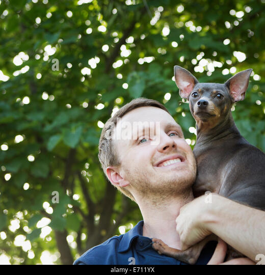 A man with a small dog on his shoulders. - Stock Image