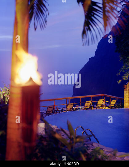 View of Petit Piton mountain at dusk from the swimming pool at Ladera Resort, Soufriere, St. Lucia. - Stock Image