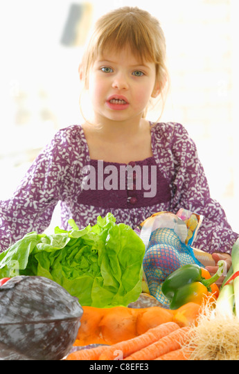 Young girl infront of a table of vegetables - Stock Image
