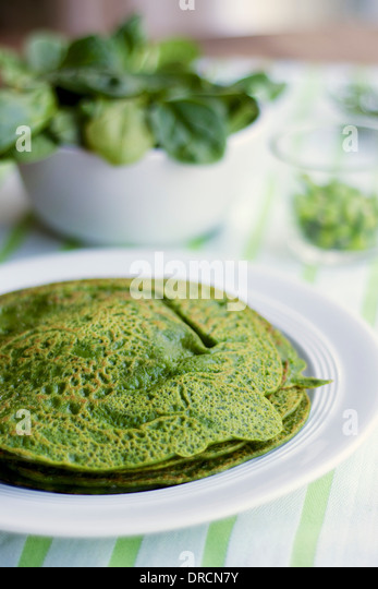 Stack of green pancakes on a plate. - Stock Image