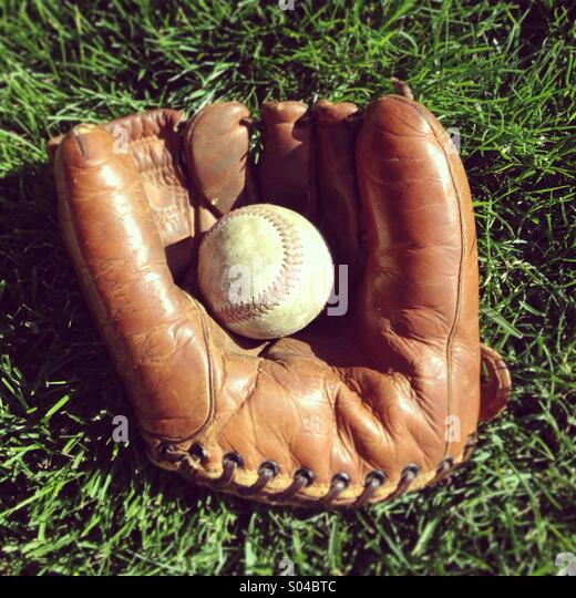 A baseball in vintage baseball mitt - Stock Image
