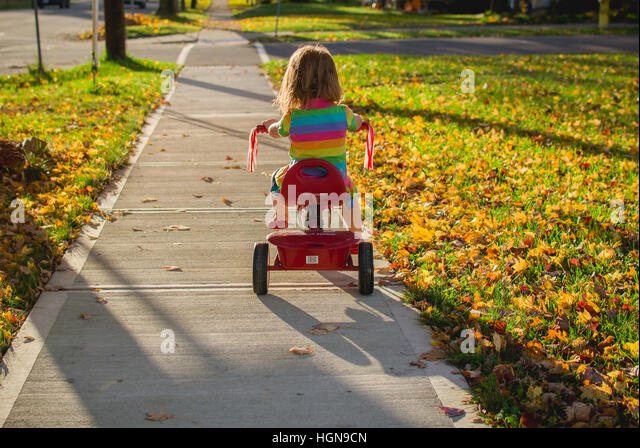 A young girl rides a tricycle in a small town in the United States. - Stock Image