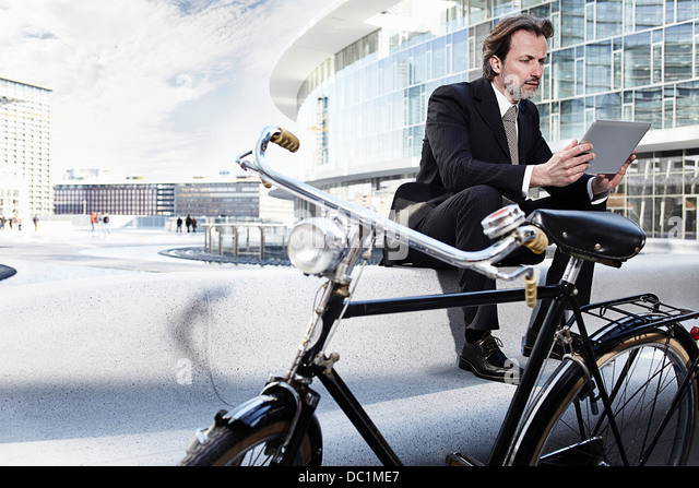 Mid adult businessman using digital tablet in city - Stock Image