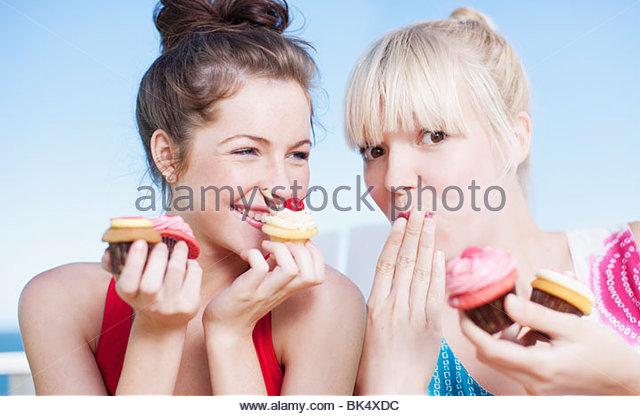 Women eating cupcakes - Stock-Bilder