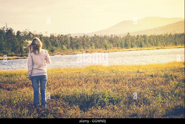 Woman Traveler walking alone Travel Lifestyle concept Summer vacations outdoor lake and mountains on background - Stock Image