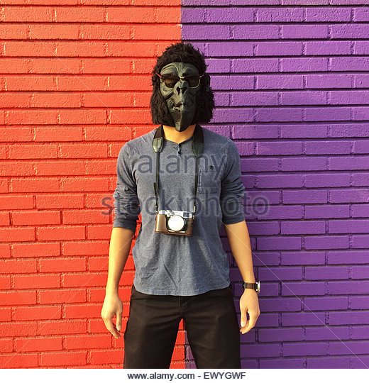 Man wearing a gorilla mask with a camera around his neck standing against a colorful brick wall - Stock Image