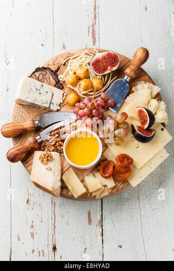 Cheese plate Assortment of various types of cheese on wooden cutting board - Stock Image