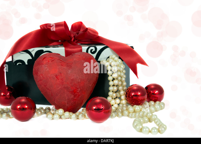 Gift with red ribbon, heart and baubles - Stock Image