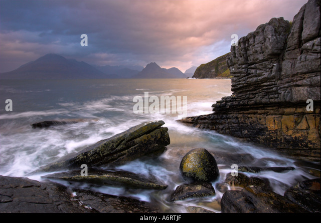 The rock strewn coast of Elgol, Isle of Skye on a dramatic morning.  High tide surges around the boulders. - Stock-Bilder