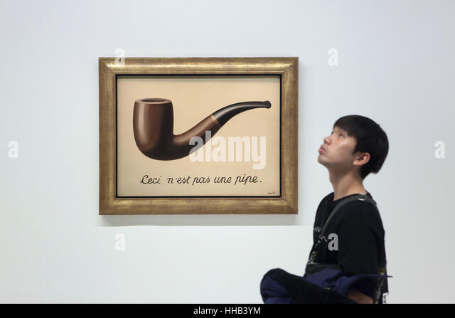 Visitor in front of the painting La trahison des images (The Treachery of Images, 1929) by Belgian surrealist artist - Stock Image
