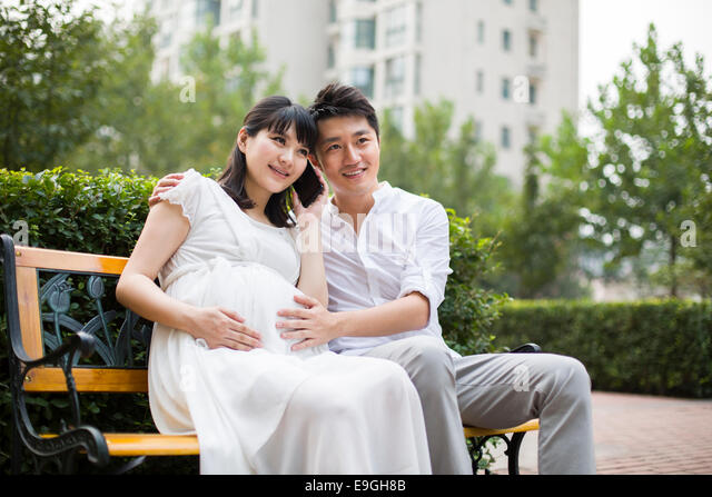 Pregnant woman using cell phone sitting beside her husband - Stock Image