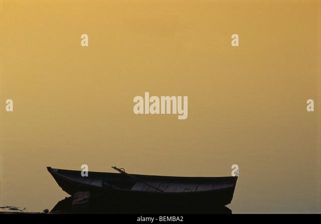 Wooden canoe on water, misty background - Stock Image