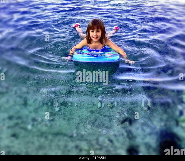 Girl swimming with surf - Stock Image