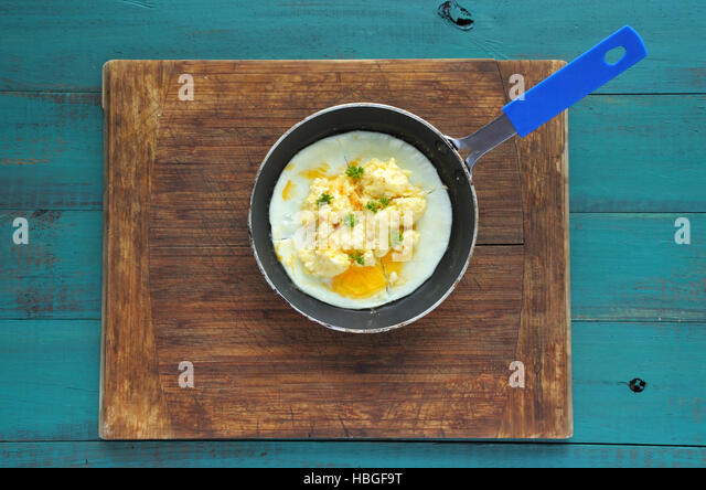 Flat lay of scrambled eggs in a rustic pen. Food background texture. copy space - Stock Image