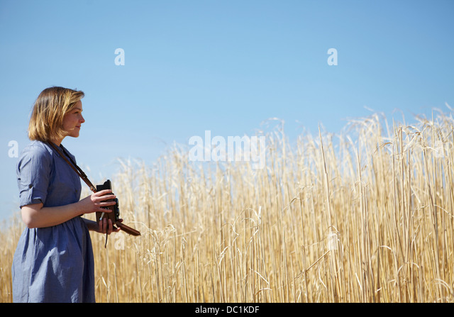 Young woman photographing reeds - Stock Image