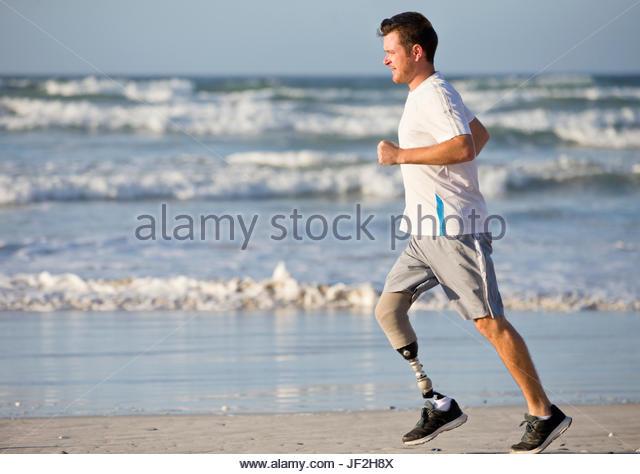 Man With Artificial Leg Running Along Beach - Stock Image