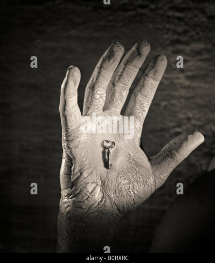 dirty hand holding small key - Stock Image