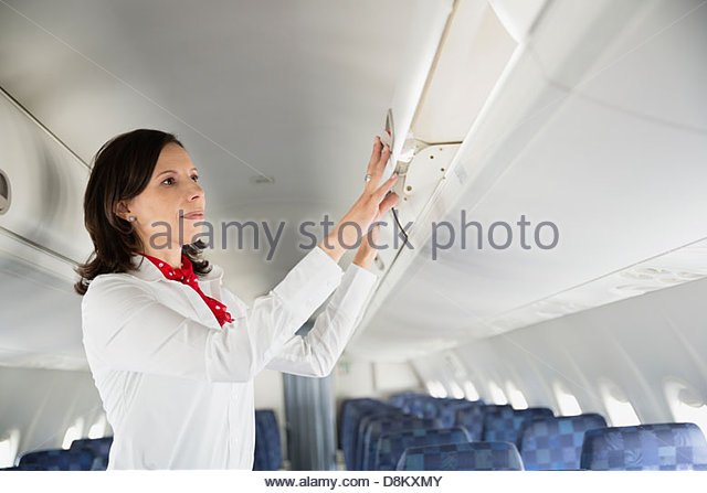 Flight attendant closing overhead bin in airplane - Stock Image