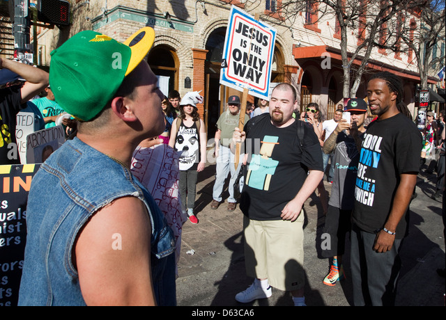 Young Hispanic homosexual male argues with a religious anti-gay white male during an outdoor festival in Austin, - Stock-Bilder