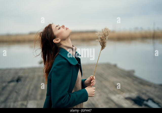 Carefree Caucasian woman standing on dock holding stalk of grass - Stock Image