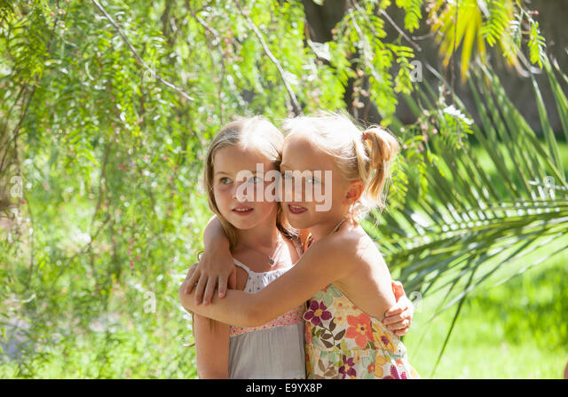 Candid portrait of two girls with arms around each other in garden - Stock Image