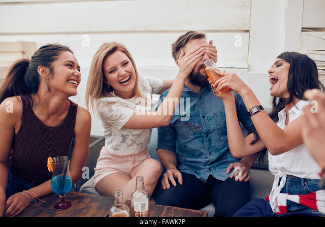 Young friends sitting together enjoying party. Woman closing eyes of a man with another giving drink. Young people - Stock Image