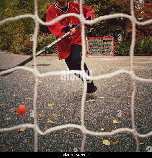 Boy playing street hockey - Stock Image