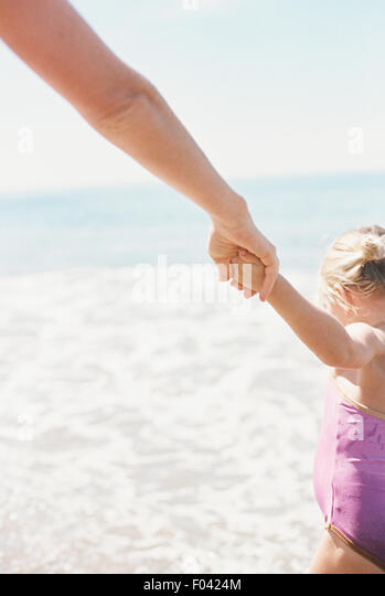 Woman and her daughter holding hands, standing on a sandy beach by he ocean. - Stock Image