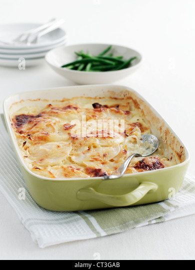 Dish of potato casserole on towel - Stock Image