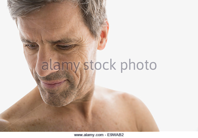 Bare chested senior man looking down - Stock Image