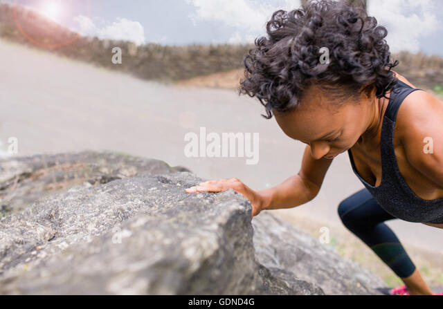 Woman climbing on rock - Stock Image
