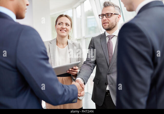 Confident employee greeting business partner with co-workers near by - Stock Image