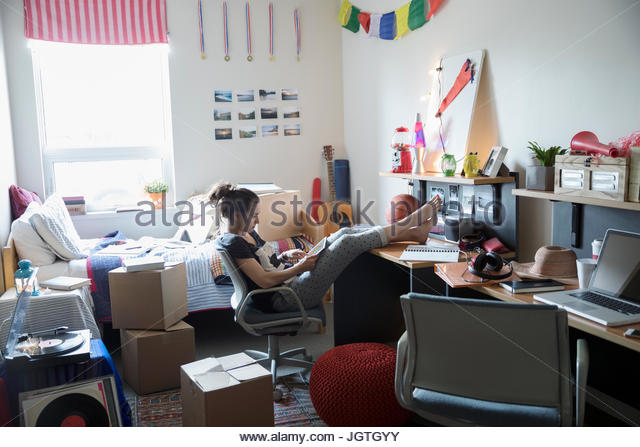 Female college student with digital tablet studying with feet up in dorm room - Stock Image