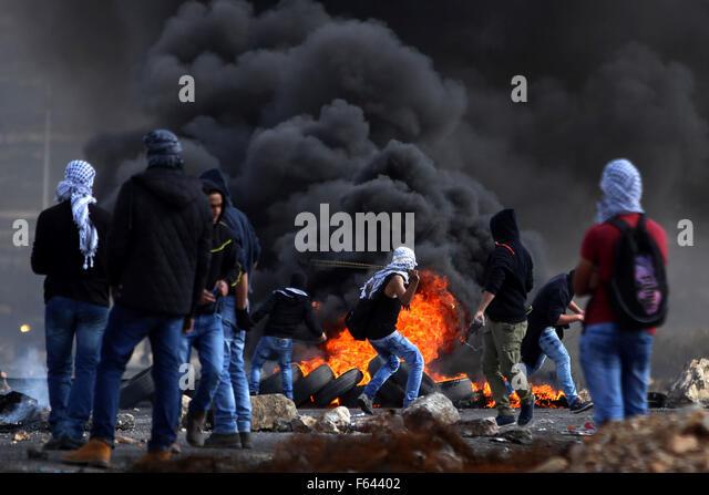 Ramallah, West Bank, Palestinian Territory. 11th Nov, 2015. Palestinian protesters throw stones towards Israeli - Stock Image