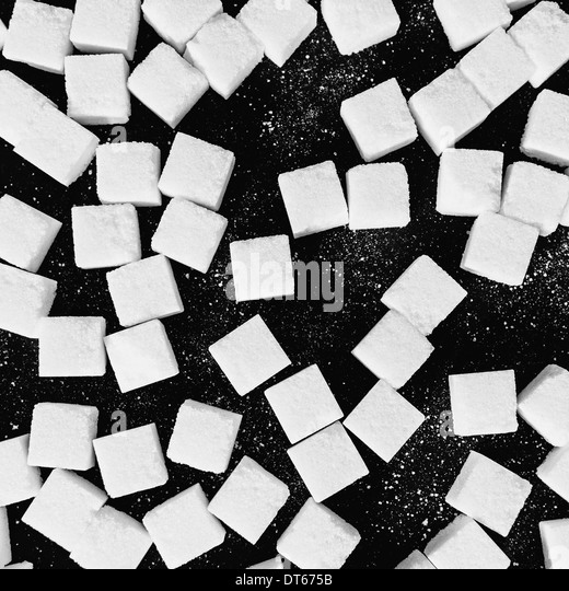 Overhead view of sugar cubes on black backdrop - Stock Image