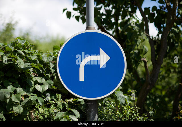 road sign on pole. turn, traffic sign, symbol, leaves. - Stock Image
