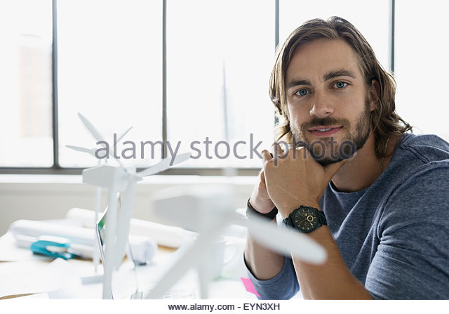 Portrait confident engineer with wind turbine models - Stock Image