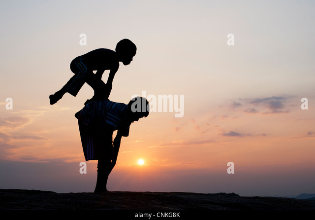 Silhouette of young Indian boys playing leap frog against at sunset. India - Stock-Bilder