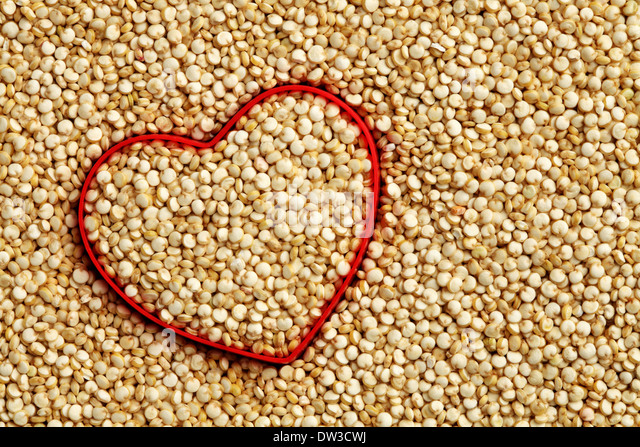 Red heart shape on uncooked quinoa background - Stock Image
