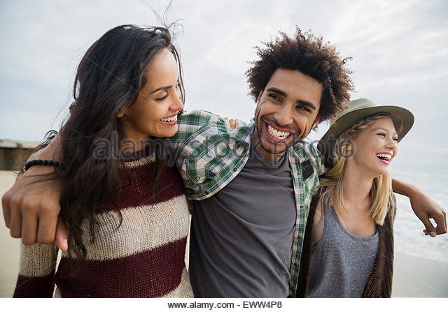 Enthusiastic friends walking on beach - Stock Image