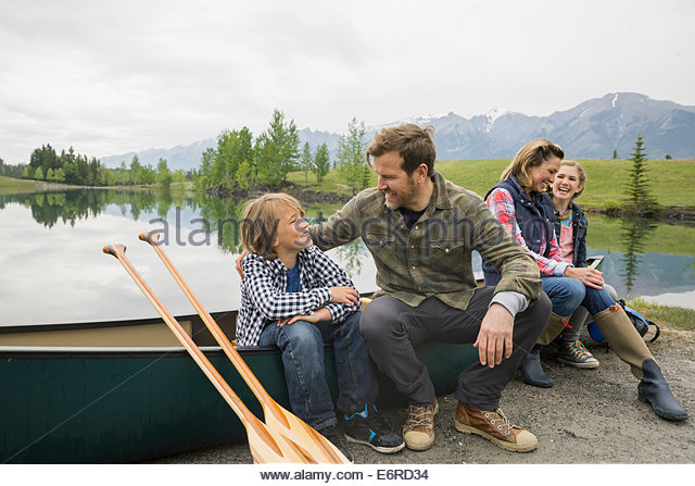 Family sitting by canoe by still lake - Stock Image