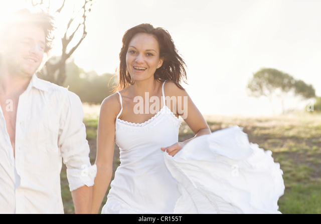 Couple walking together in field - Stock Image