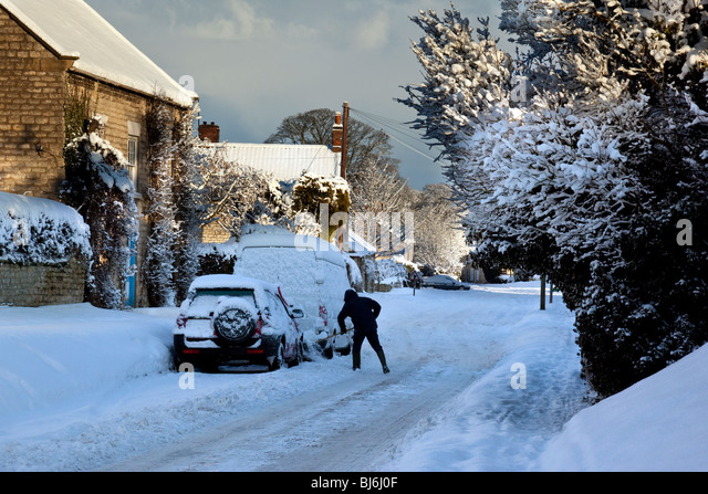 Clearing winter snow from vehicles in the small village of Slingsby in North Yorkshire in the United Kingdom - Stock Image